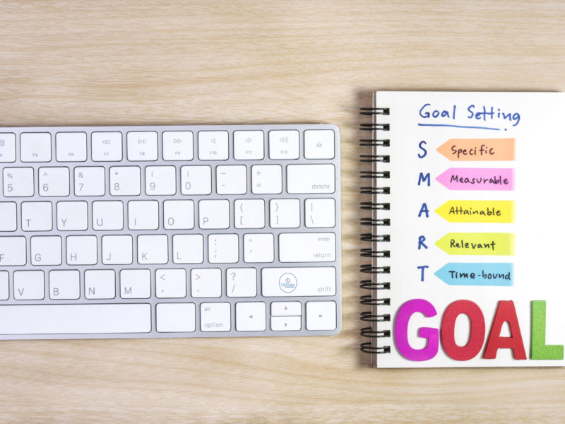 smart goals setting written on the notebook and keyboard over wooden table, business success concept